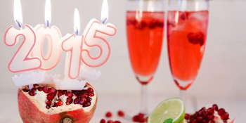 Two glasses with red champagne and candles 2015